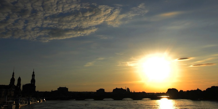 The sun goes down behind the wide river of the Elbe in the old town of Dresden, Germany, Wednesday.