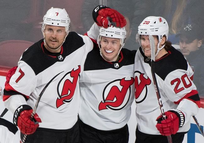 New Jersey Devils' Blake Coleman (20) celebrates with teammates Nikita Gusev and Matt Tennyson (7) after scoring against the Montreal Canadiens during first period NHL hockey action in Montreal, Thursday, November 28, 2019. THE CANADIAN PRESS/Graham Hughes
