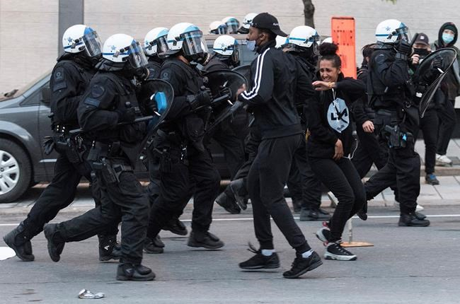 Police push back protesters during a demonstration calling for justice in the death of George Floyd and victims of police brutality in Montreal, Sunday, May 31, 2020.THE CANADIAN PRESS/Graham Hughes