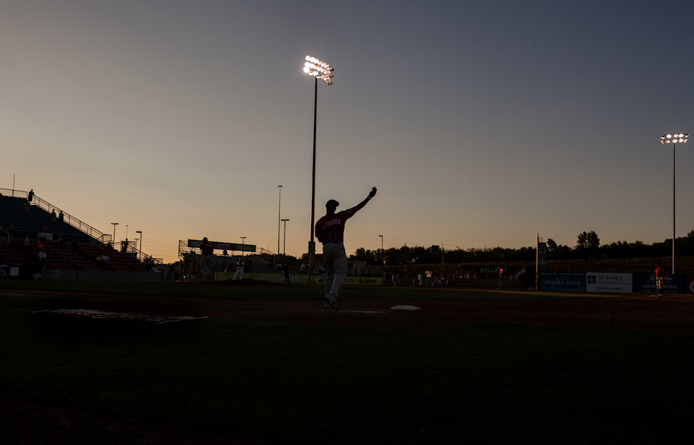 First baseman Yurendell de Caster tosses the ball to second base at dusk during an inning warmup during the Sunday game in Sioux City. (Melissa Tait / Winnipeg Free Press)