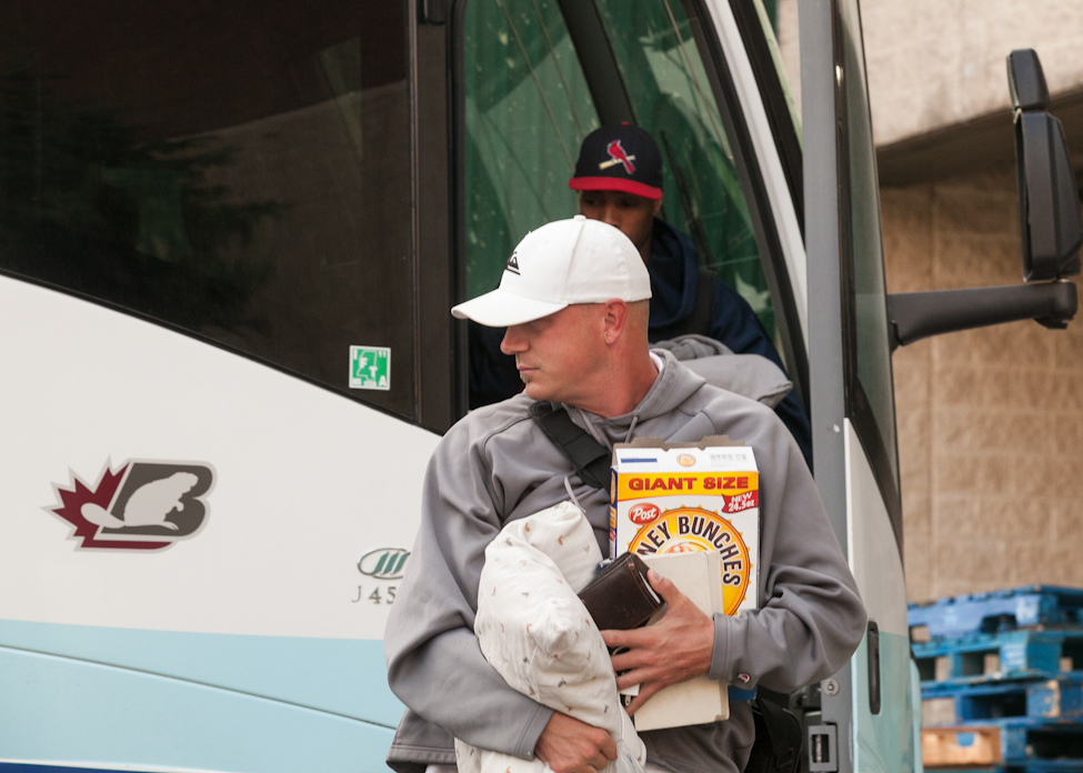 Pitcher Ace Walker leaves the bus with breakfast and pillow in hand when the Goldeyes' bus arrived just after daybreak Monday morning.