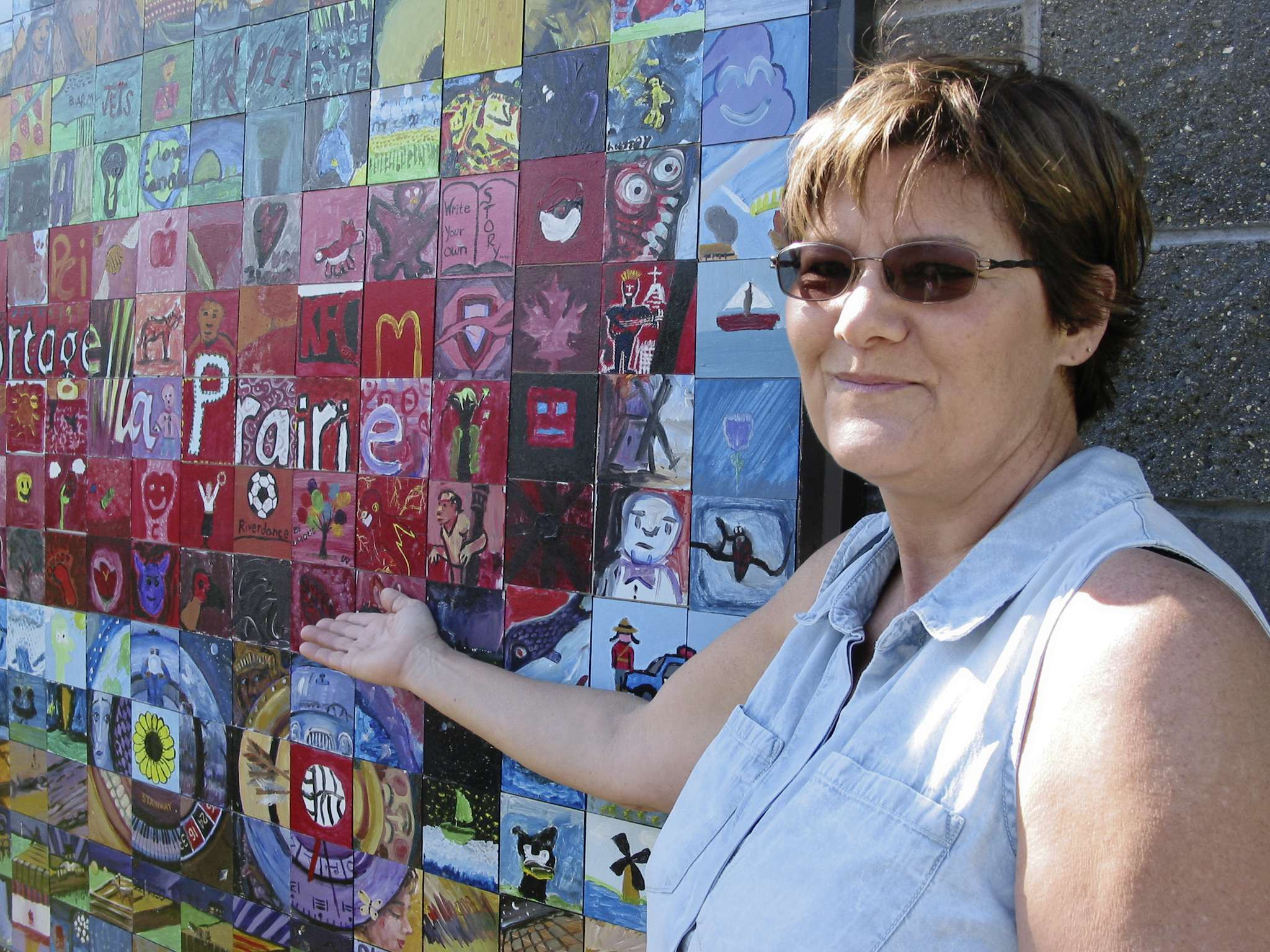 Carole Lupkowski, Portage la Prairie Public Art Committee  member, shows some of the over 260 tiles that were combined to form the community's Canada 150 mosaic on the north wall of Stride Place.