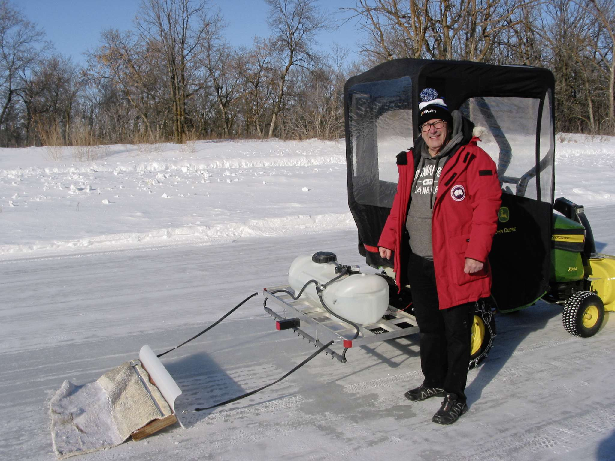 Paul Brault is shown here with the ice-clearing machine that he created to provide a smooth ice surface for skating on the retention pond behind his Deer Pointe home in Headingley.