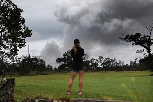 Marie Brant, of Laguna Niguel, Calif., watches as ash rises from the summit crater of Kilauea volcano, Thursday, May 17, 2018, in Volcano, Hawaii. Brant is on vacation in Hawaii. The volcano on Hawaii's Big Island erupted anew Thursday shortly after 4 a.m. with little sound and only modest fury, spewing a steely gray plume of ash about 30,000 feet into the sky that began raining down on a nearby town. (AP Photo/Caleb Jones)