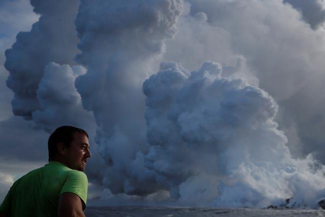 Joe Kekedi watches as lava enters the ocean, generating plumes of steam near Pahoa, Hawaii Sunday, May 20, 2018. Kilauea volcano that is oozing, spewing and exploding on Hawaii's Big Island has gotten more hazardous in recent days, with rivers of molten rock pouring into the ocean Sunday and flying lava causing the first major injury. (AP Photo/Jae C. Hong)