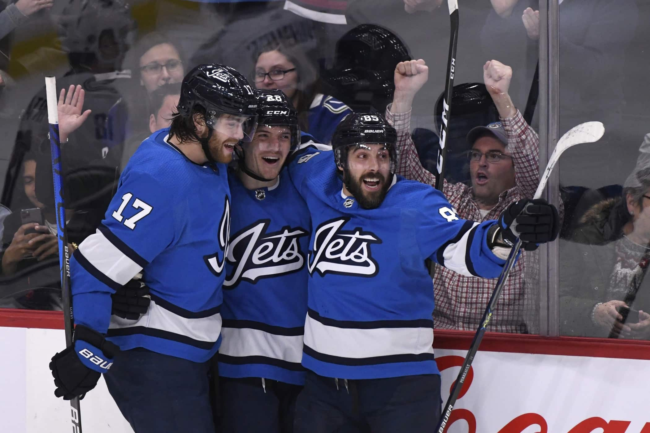 From left, Winnipeg Jets' Adam Lowry (17), Jack Roslovic (28) and Mathieu Perreault (85) celebrates Roslovic's goal during first period NHL action against the Vancouver Canucks. (Fred Greenslade / Canadian Press)