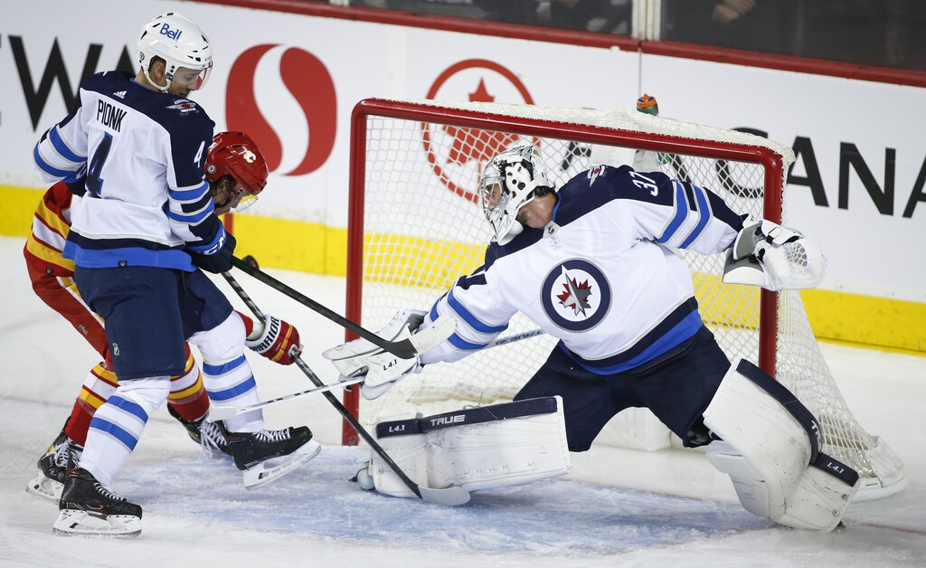 Connor Hellebuyck and Neal Pionk keep Calgary's Rasmus Andersson from putting the puck in the net during the second period. (Jeff McIntosh / The Canadian Press)