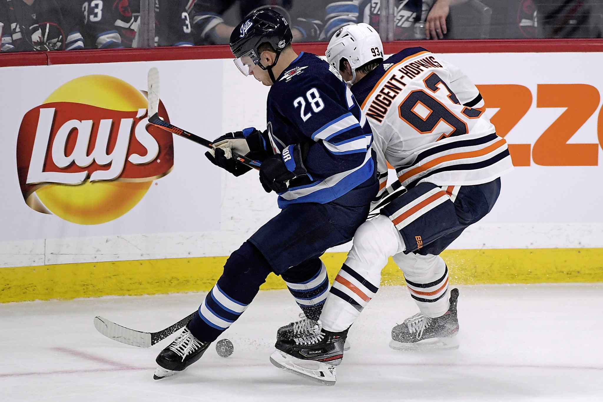 Winnipeg Jets' Jack Roslovic (28) and Edmonton Oilers' Ryan Nugent-Hopkins (93) chase a loose puck during the first period Sunday.