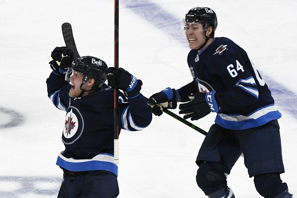 Logan Stanley (right) celebrates Nikolaj Ehlers' game-winning goal in the first overtime period against the Edmonton Oilers in Winnipeg on Sunday. (Fred Greenslade / Canadian Press files)