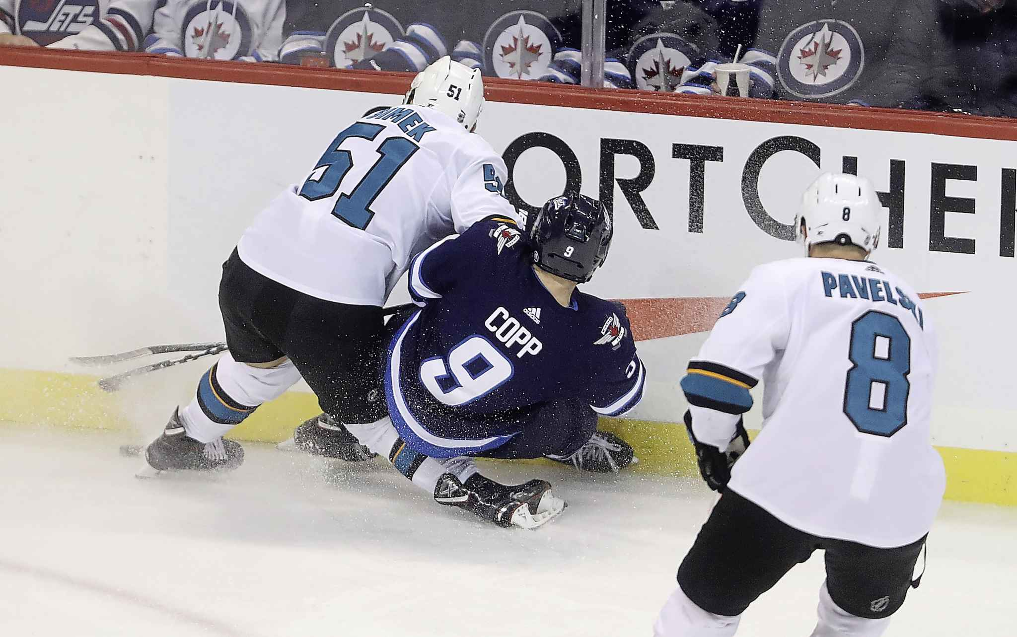 San Jose Sharks' Radim Simek suffers a leg injury as Winnipeg Jets' Andrew Copp falls on it during the first period Tuesday. TREVOR HAGAN / THE CANADIAN PRESS