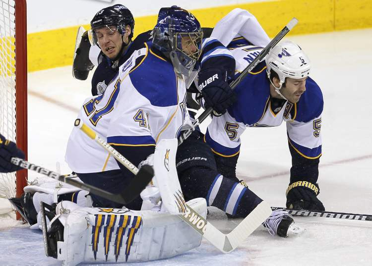 Winnipeg Jets' Kyle Wellwood is sandwiched between St. Louis Blues Barret Jackman and goalie Jaroslav Halak in the first period Saturday.