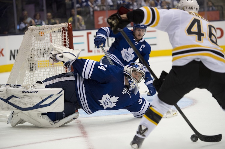 Toronto Maple Leafs goaltender James Reimer makes a diving save while defenceman Dion Phaneuf protects the net as Boston Bruins David Krejci attempts a shot during the third period of Wednesday night's game in Toronto.