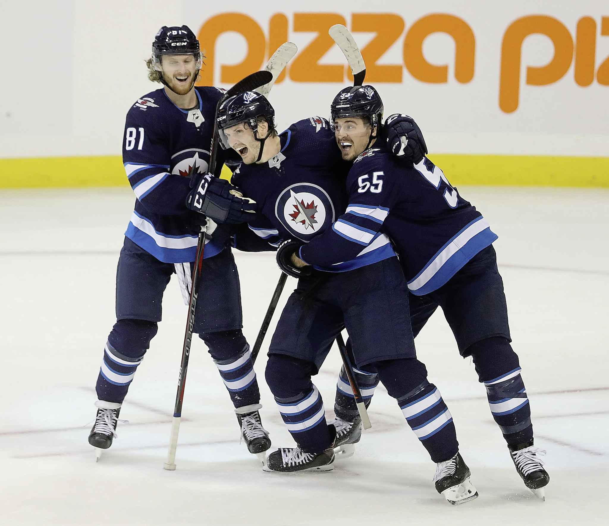 Winnipeg Jets' Kyle Connor (81), Jacob Trouba (8), and Mark Scheifele (55) celebrate after Trouba scored the game-winning goal against the St. Louis Blues. (Trevor Hagan / The Canadian Press)