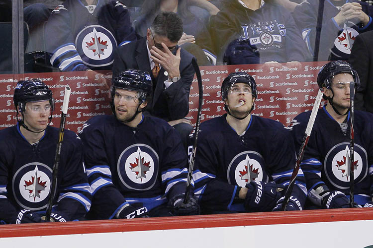 Winnipeg Jets' head coach Claude Noel bows his head in disappointment during the third period.