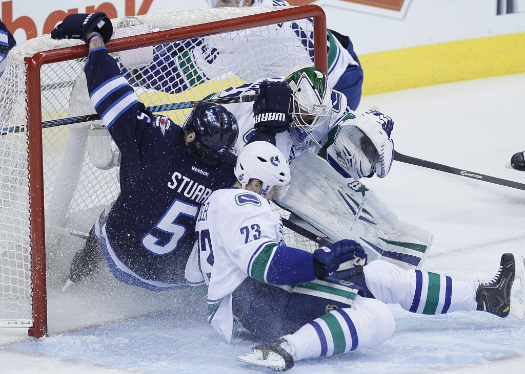 Winnipeg Jets' Mark Stuart (5) and Vancouver Canucks' Alexander Edler (23) crash into Canucks goaltender Eddie Lack (31).