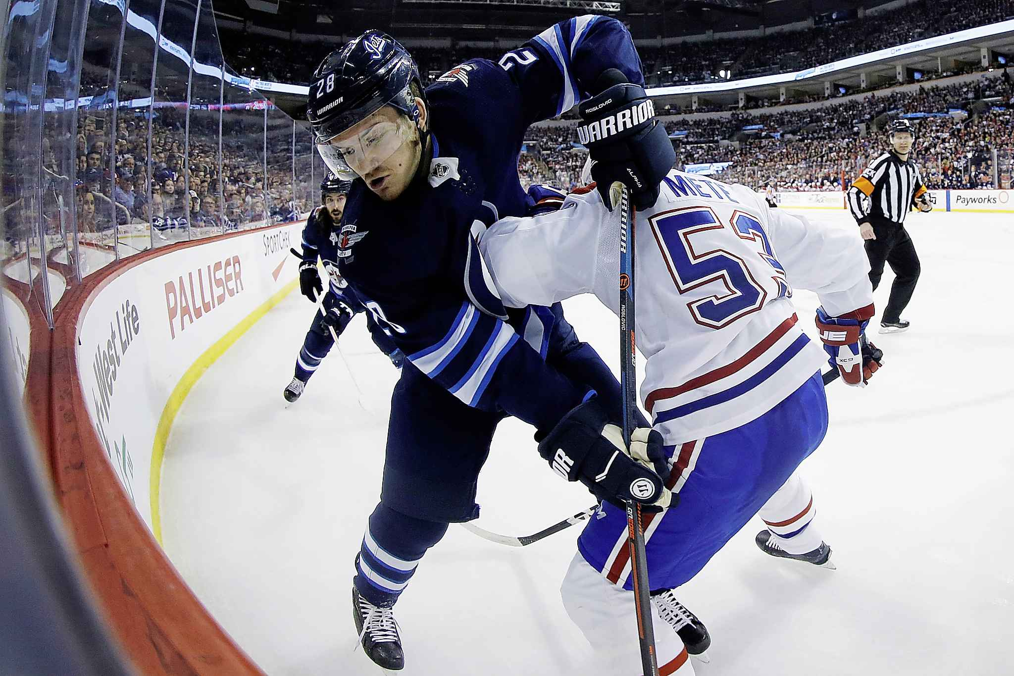 "JOHN WOODS / THE CANADIAN PRESS</p> <p>Winnipeg Jets' Jack Roslovic (28) and Montreal Canadiens' Victor Mete (53) fight for possession of the puck during second period NHL action in Winnipeg on Saturday, March 28, 2019.</p> <p>""></a><figcaption readability="