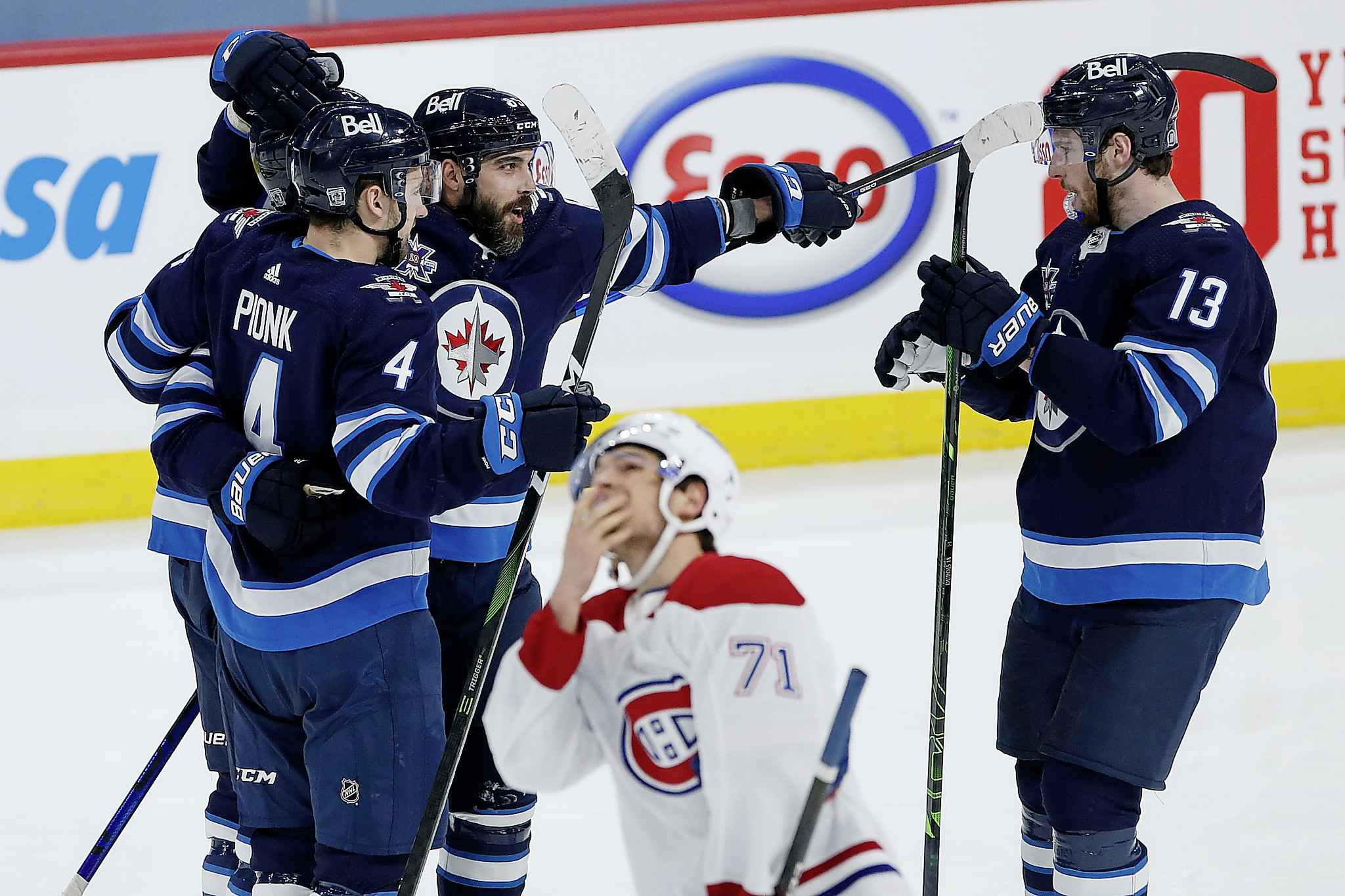 Winnipeg Jets' Neal Pionk (4), Nikolaj Ehlers (27), Mathieu Perreault (85) and Pierre-Luc Dubois (13) celebrate Ehlers' goal as Montreal Canadiens' Jake Evans (71) skates past during second period NHL action in Winnipeg on Saturday, February 27, 2021. (John Woods / The Canadian Press)