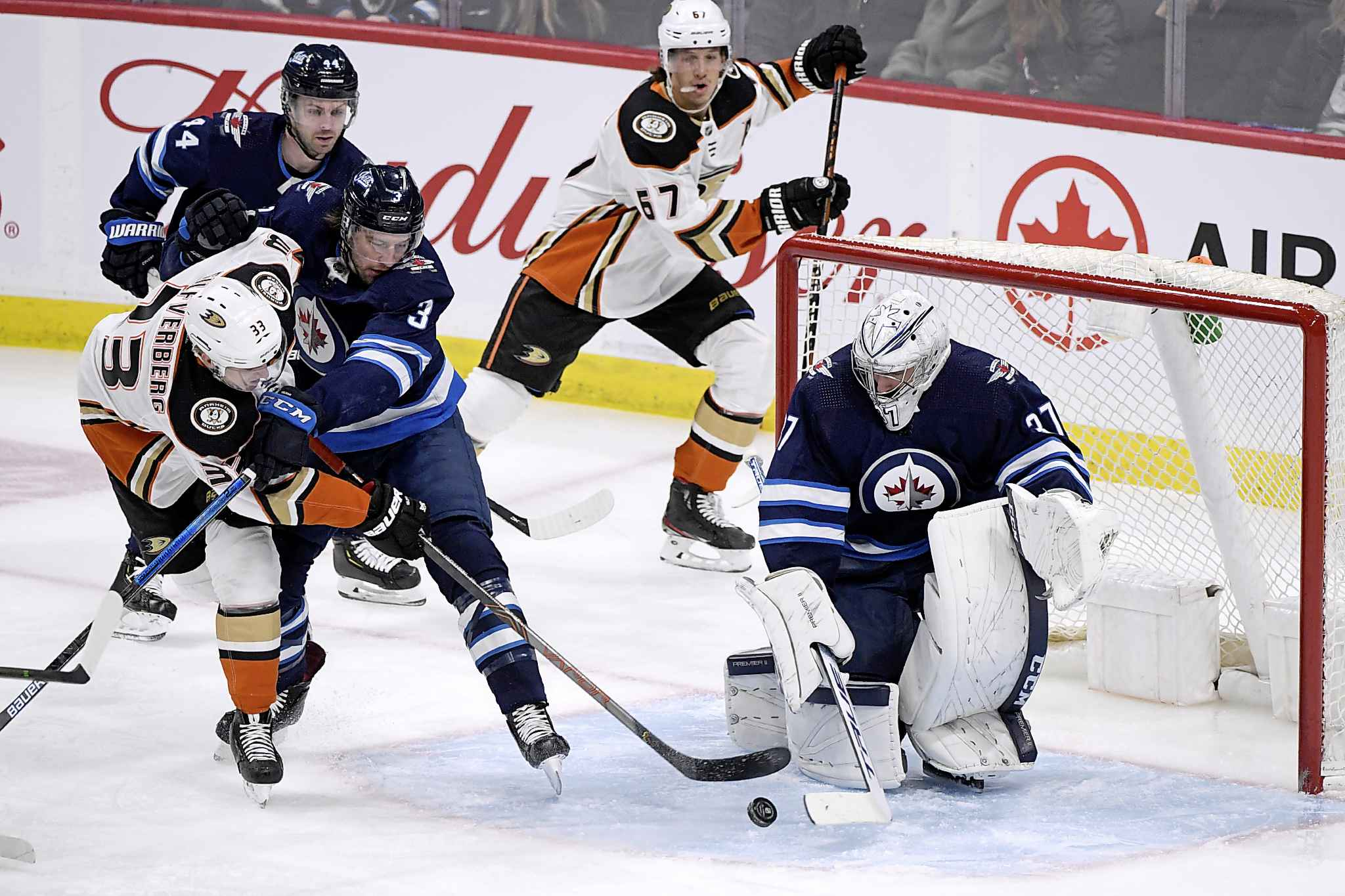 Winnipeg Jets goaltender Connor Hellebuyck (37) sweeps aside a shot by Anaheim Ducks' Jakob Silfverberg (33) as Tucker Poolman (3) defends during the first period. (Fred Greenslade / The Canadian Press)</p>