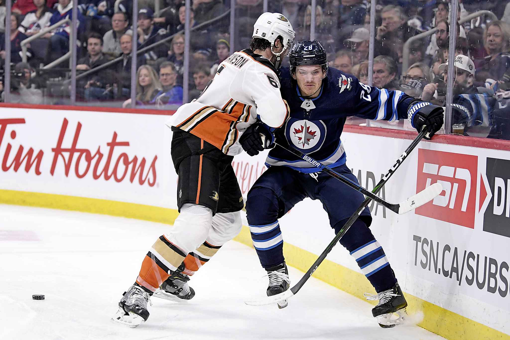 Winnipeg Jets' Jack Roslovic (28) braces for the hit as Anaheim Ducks' Erik Gudbranson (6) checks him into the boards during the second period. (Fred Greenslade / The Canadian Press)</p>