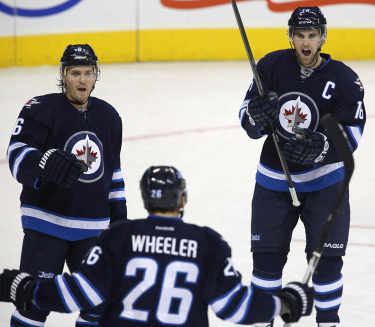 Winnipeg Jets' Ron Hainsey, Blake Wheeler and Andrew Ladd celebrate after Ladd's goal against the Philadelphia Flyers during the first period at MTS Centre. (Trevor Hagan / The Canadian Press)