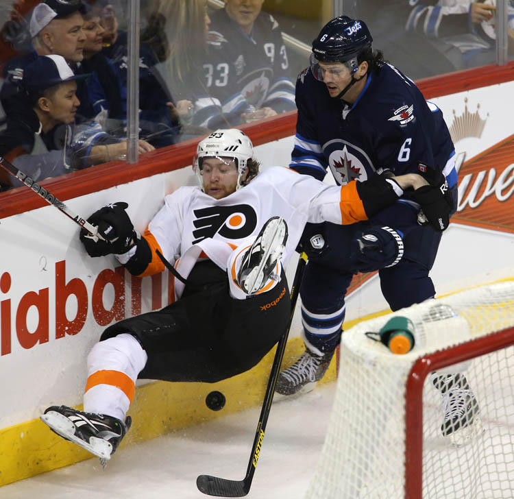 Philadelphia Flyers' Jakub Voracek is tripped up by Winnipeg Jets' Ron Hainsey behind the Jets' goal during the second period.  (Trevor Hagan / The Canadian Press)