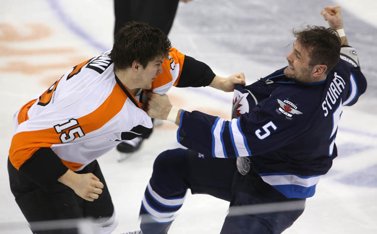 Winnipeg Jets' Mark Stuart flails for a final punch during a fight with Philadelphia Flyers' Tye McGinn in the second period at MTS Centre Tuesday night. (Trevor Hagan / The Canadian Press)