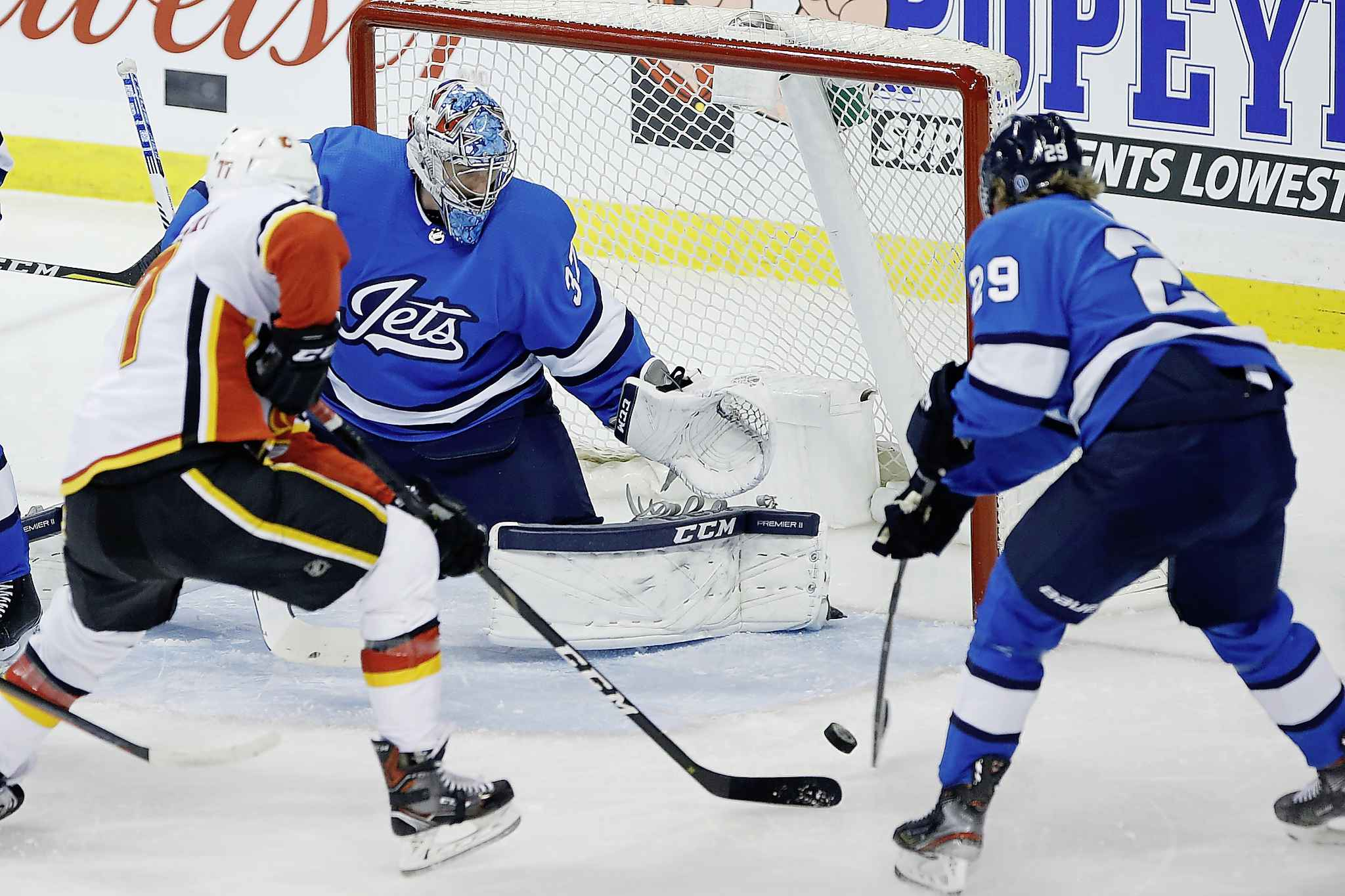 JOHN WOODS / THE CANADIAN PRESS</p><p>Winnipeg Jets goaltender Connor Hellebuyck (37) saves the shot by Calgary Flames' Mark Jankowski (77) during first period NHL action.</p>