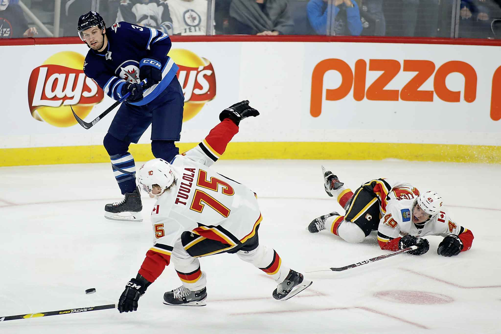FRED GREENSLADE / THE CANADIAN PRESS</p><p>Winnipeg Jets' Tucker Poolman (3) passes the puck past Calgary Flames' Eetu Tuulola (75) and teammate Jakob Pelletier (49) during first period NHL action in Winnipeg on Sunday, Sept. 22, 2019.</p>
