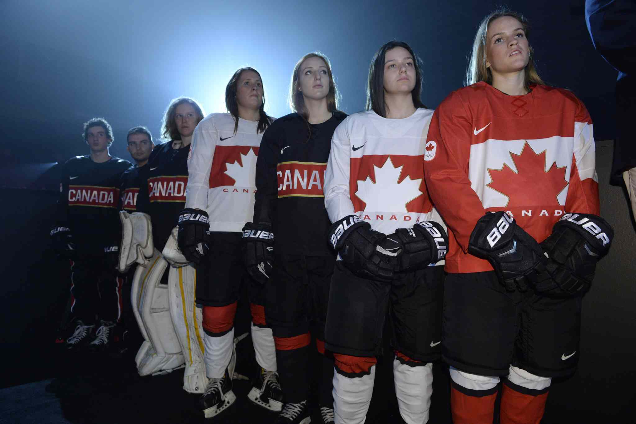 Youth players model the new Canadian Olympic team hockey jerseys at Tuesday's official unveiling in Toronto.