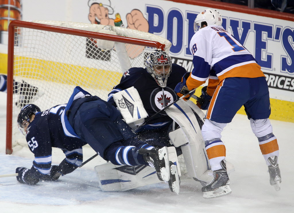 Winnipeg Jets' Mark Scheifele (55) is shoved into goaltender Ondrej Pavelec (31) by New York Islanders' Ryan Strome (18) during first period NHL hockey action in Winnipeg, Tuesday, March 4, 2014.  (Trevor Hagan / THE CANADIAN PRESS)