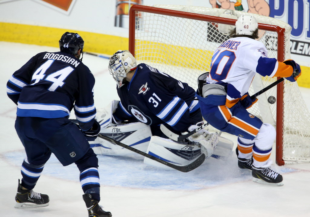 New York Islanders' Michael Grabner (40) scores a game winning goal on Winnipeg Jets goaltender Ondrej Pavelec (31) as Zach Bogosian (44) looks on, during overtime.  (Trevor Hagan / THE CANADIAN PRESS)