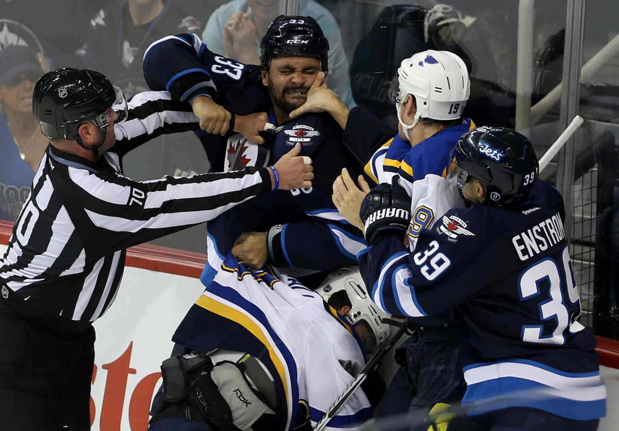 Winnipeg Jets blue-liner Dustin Byfuglien scrums with the St. Louis Blues' Scottie Upshall and Jay Bouwmeester (19) as diminutive Jets defenceman Toby Enstrom tries to make his presence felt.