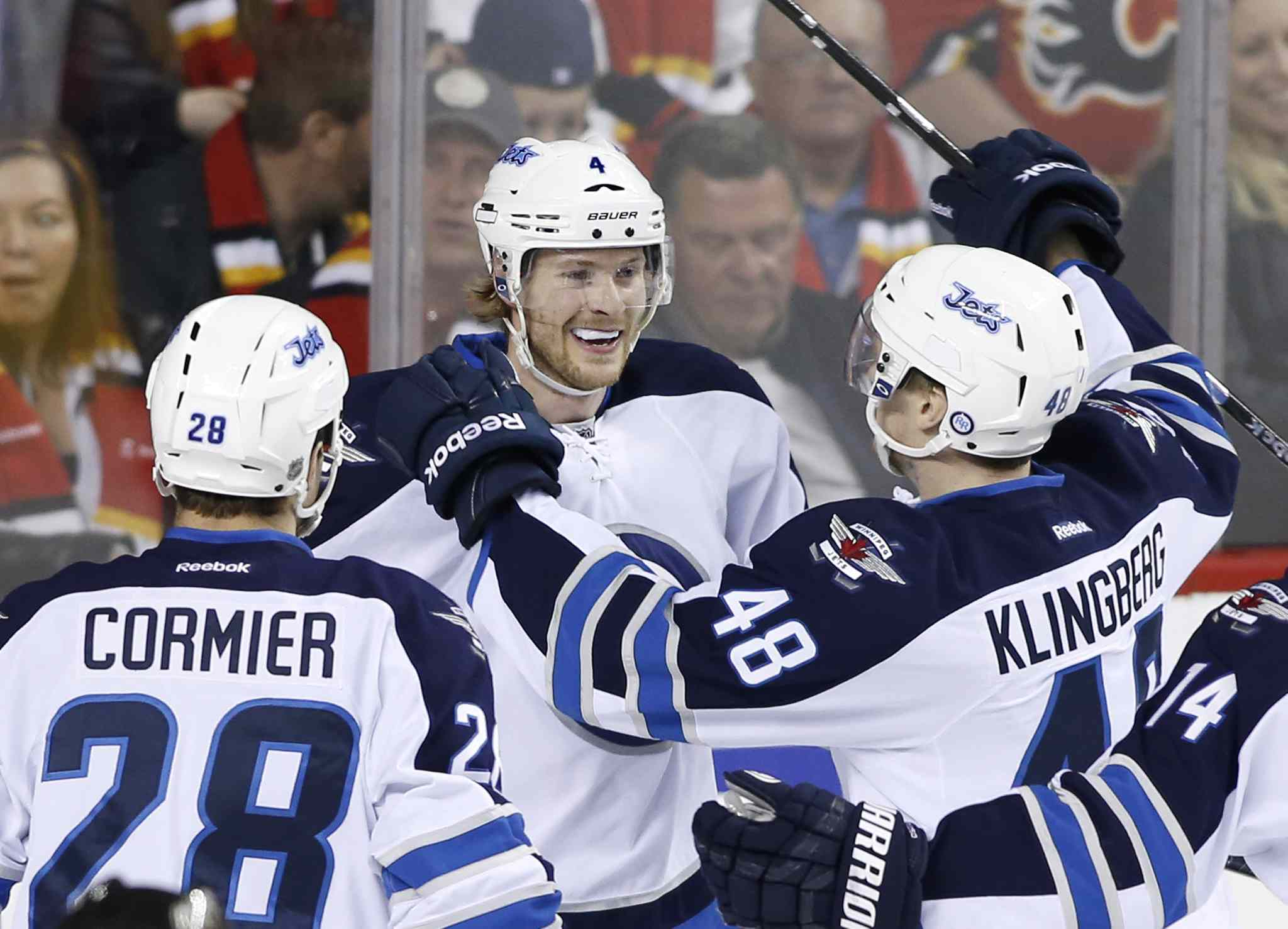 Winnipeg Jets' Paul Postma, centre, celebrates his game winning goal against the Calgary Flames' with Patrice Cormier, left, and Carl Klingberg, from Sweden, during third period NHL action in Calgary, Alta., April 11, 2014.