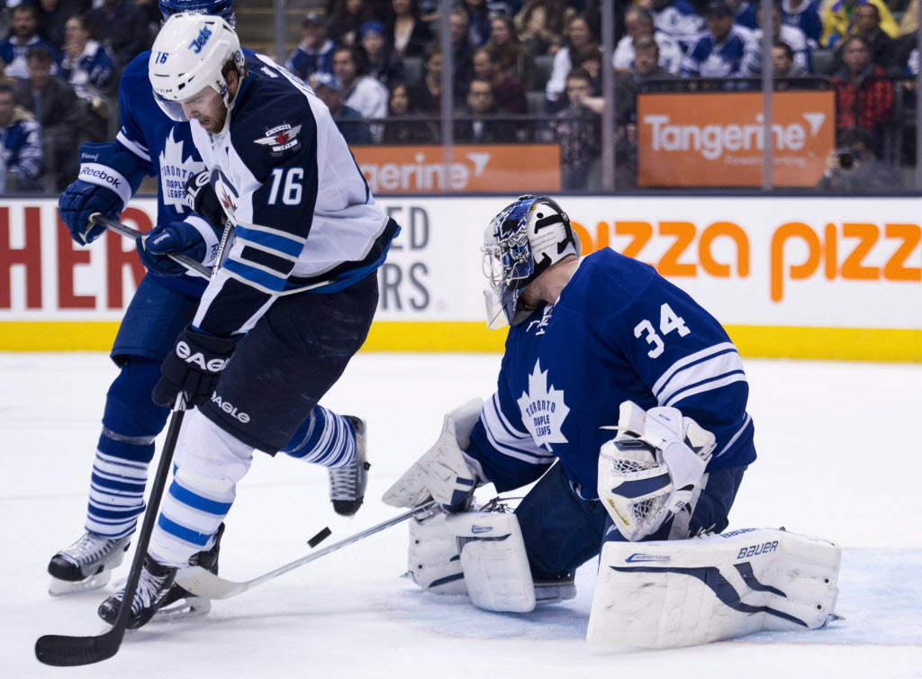 Toronto Maple Leafs goalie James Reimer (34) makes a save as he is screened by Winnipeg Jets forward Andrew Ladd (16).  (Nathan Denette / The Canadian Press)