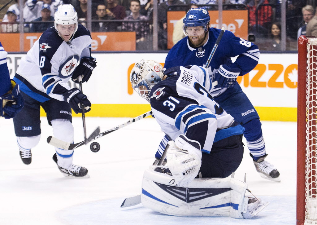 Winnipeg Jets goalie Ondrej Pavelec (31) eyes the loose puck as Toronto Maple Leafs forward Phil Kessel (back right) and Jets defenceman Jacob Trouba (8) battle for the loose puck. (Nathan Denette / The Canadian Press)
