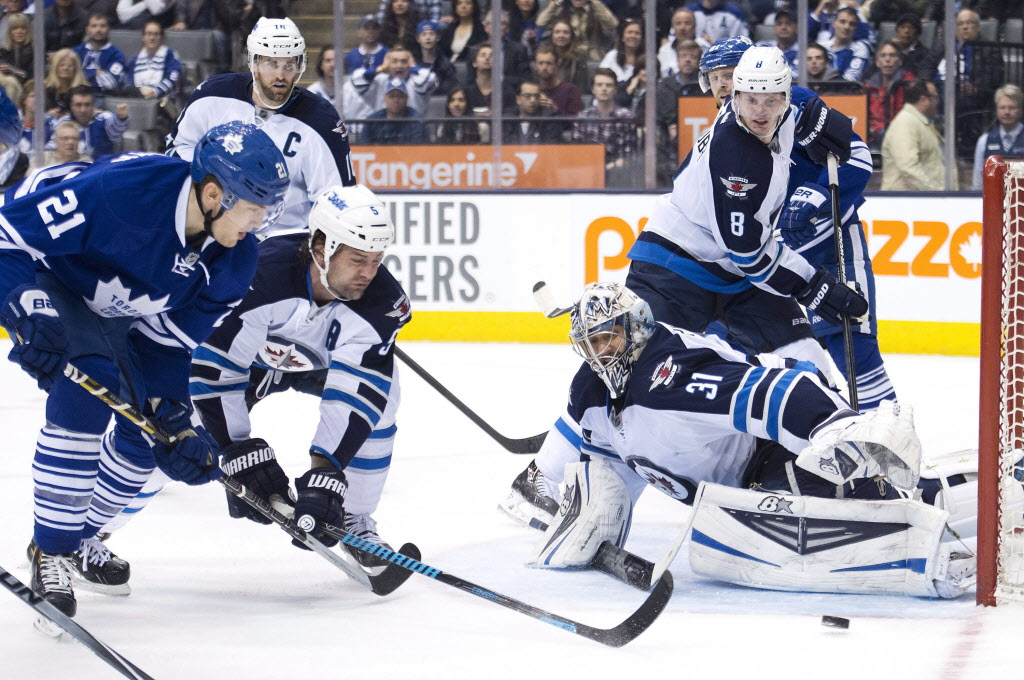 Winnipeg Jets goalie Ondrej Pavelec (31) makes a save as Toronto Maple Leafs forward James van Riemsdyk (21) and Jets defenceman Mark Stuart (5) battle for the loose puck during. (Nathan Denette / The Canadian Press)