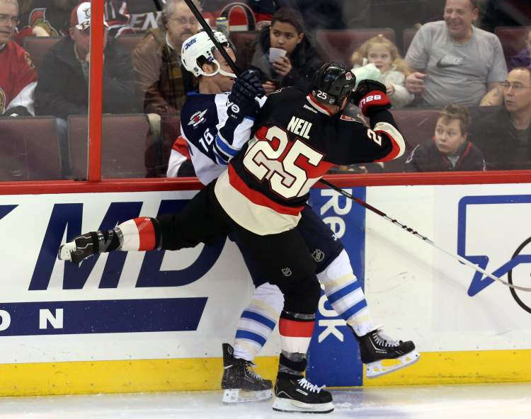 Winnipeg Jets Andrew Ladd (16) is checked by Ottawa Senators Chris Neil (25) during first period NHL hockey between the Ottawa Senators and the Winnipeg Jets in Ottawa Saturday February 9, 2013.  (Fred Chartrand / The Canadian Press)