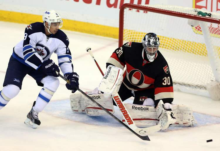 Winnipeg Jets Evander Kane (9) tries to reach for a loose puck as ottawa Senators goaltender Ben Bishop (30) looks on during first period NHL hockey between the Ottawa Senators and the Winnipeg Jets in Ottawa Saturday.  (Fred Chartrand / The Canadian Press)