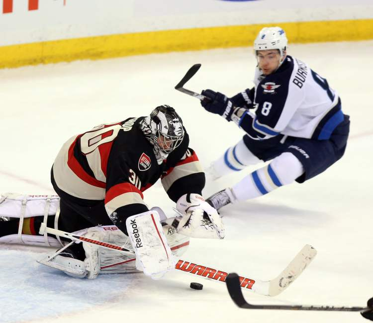 Ottawa Senators goaltender Ben Bishop (30) dives for a loose puck as Winnipeg Jets Alexander Burmistroc (8) looks on during second period NHL hockey between the Ottawa Senators and the Winnipeg Jets in Ottawa Saturday.  (Fred Chartrand / The Canadian Press)