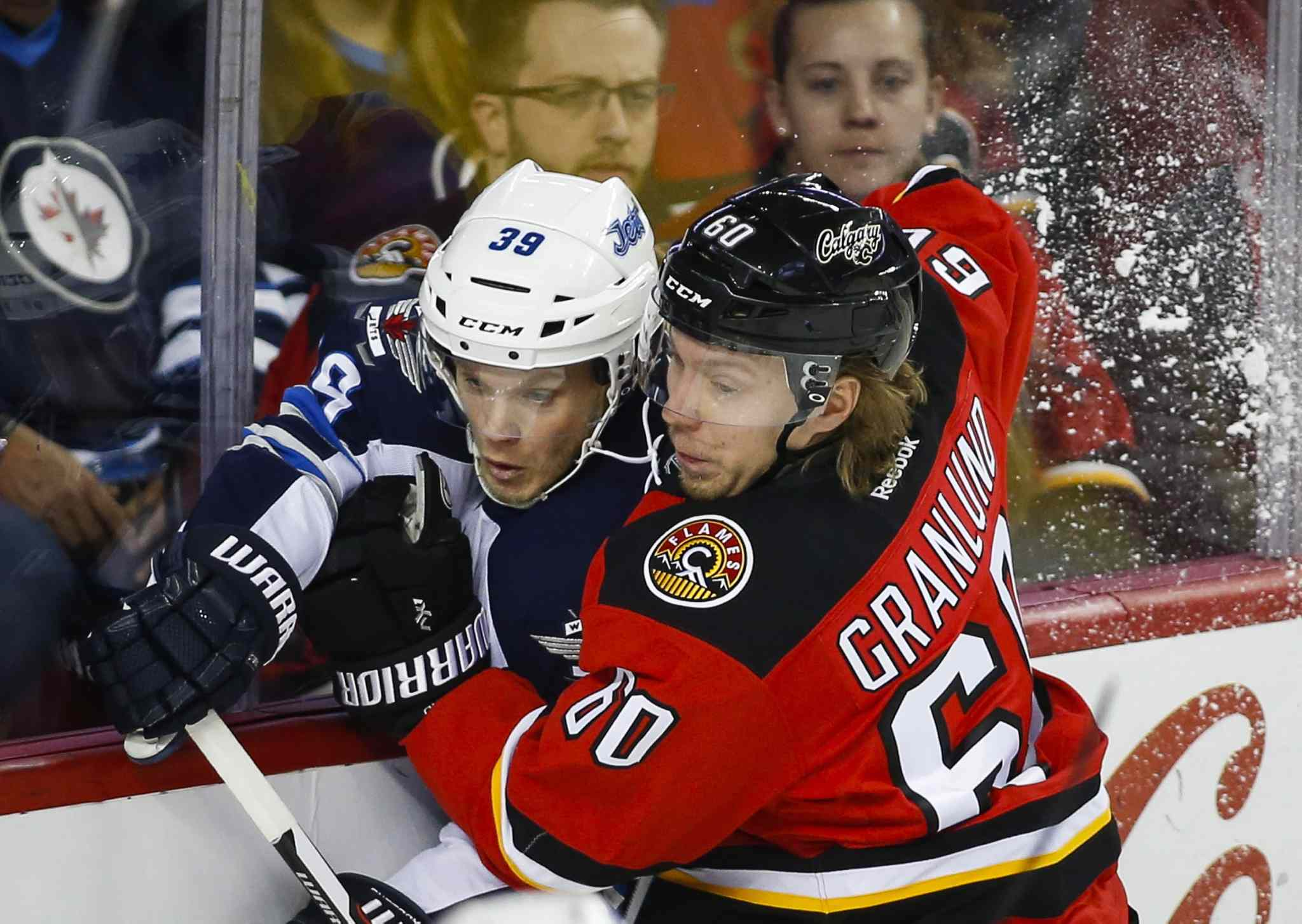 Winnipeg Jets' Tobias Enstrom, left, of Sweden, is checked by Calgary Flames' Markus Granlund, from Finland, during first period NHL hockey action in Calgary, Tuesday, Dec. 22, 2015.THE CANADIAN PRESS/Jeff McIntosh