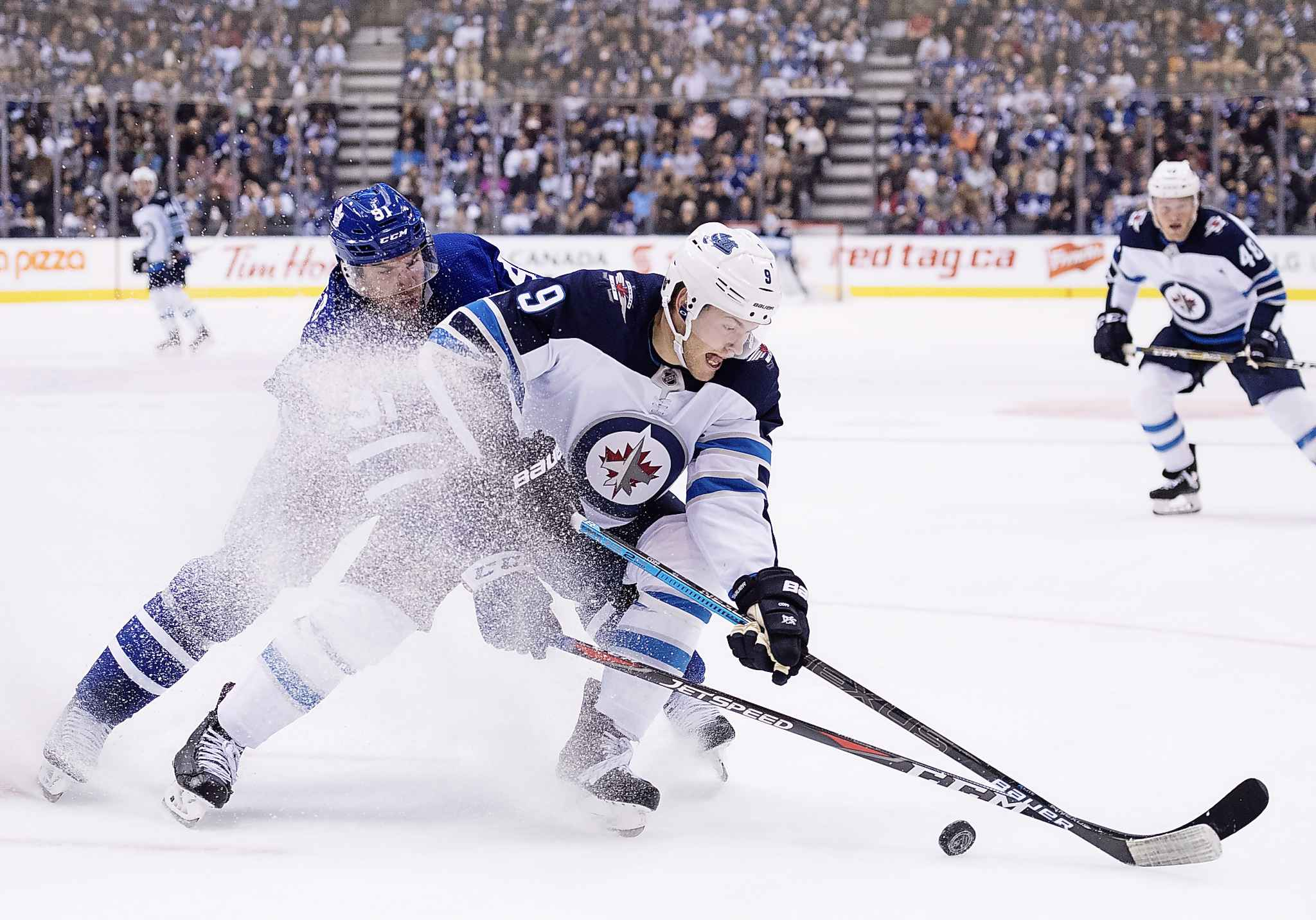 Toronto Maple Leafs centre John Tavares (91) and Winnipeg Jets centre Andrew Copp (9) battles for the puck during second period NHL hockey action in Toronto on Saturday, October 27, 2018. THE CANADIAN PRESS/Nathan Denette