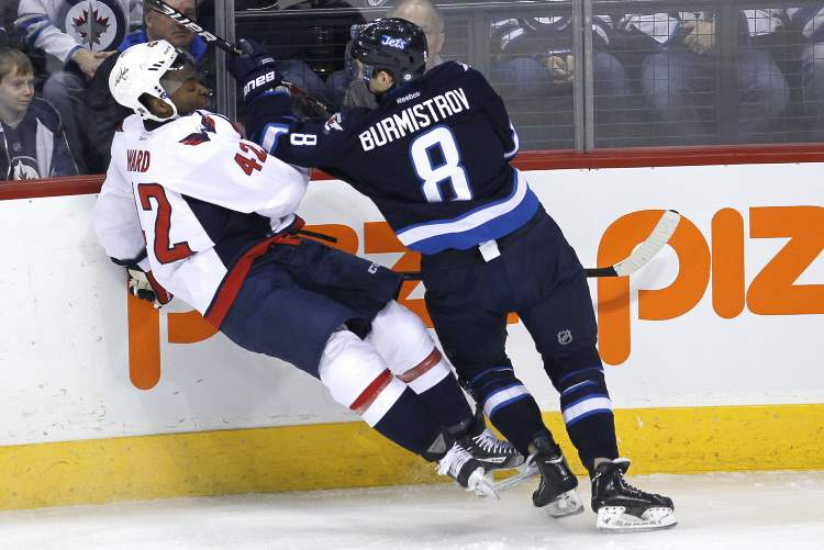 Alexander Burmistrov checks the Washington Capitals' Joel Ward hard during first-period action Saturday afternoon.