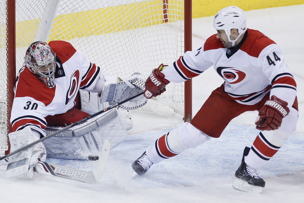 Carolina Hurricanes goaltender Cam Ward (30) stops the shot from Winnipeg Jets' Evander Kane (9) as Jay Harrison (44) looks on during first period NHL action in Winnipeg on Saturday, March 22, 2014.