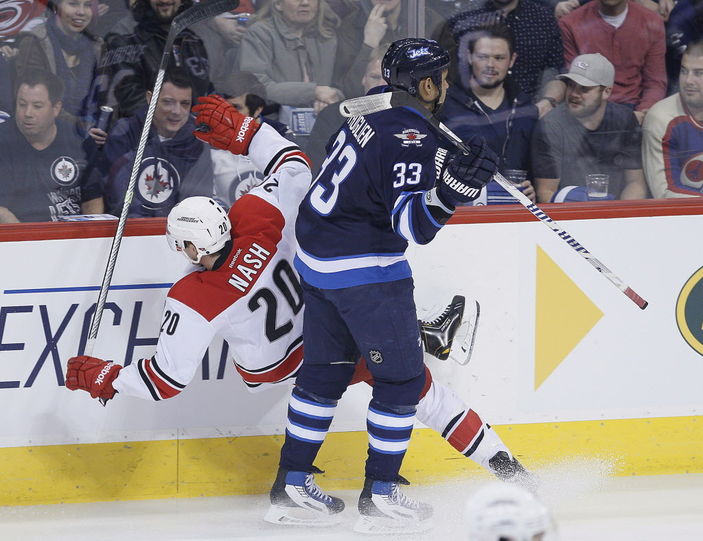 Winnipeg Jets' Dustin Byfuglien (33) dumps Carolina Hurricanes' Riley Nash (20) during first period NHL action in Winnipeg on Saturday. (JOHN WOODS / THE CANADIAN PRESS)