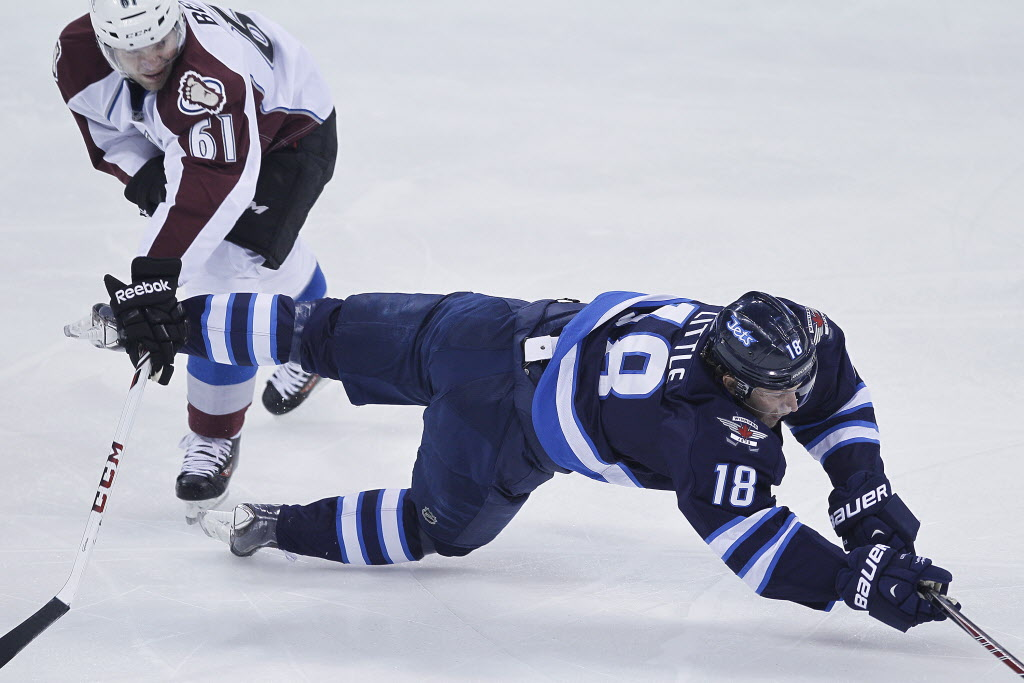 Colorado Avalanche's Andre Benoit (61) trips Winnipeg Jets' Bryan Little (18) during first period NHL action in Winnipeg on Wednesday, March 19, 2014. THE CANADIAN PRESS/John Woods (CP)