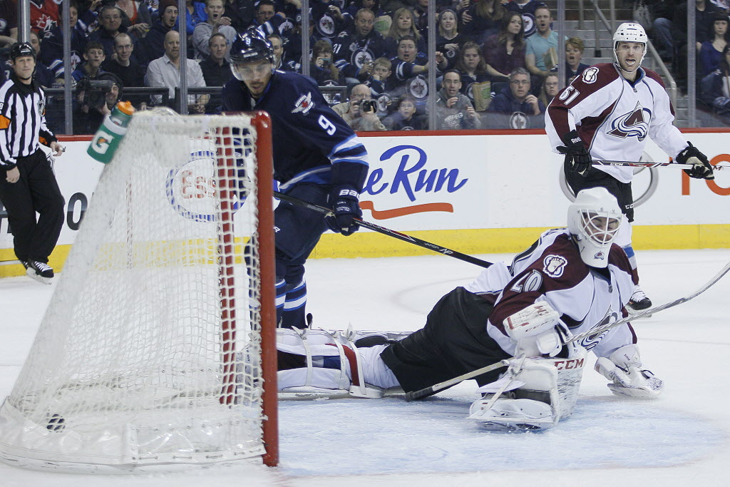 Winnipeg Jets' Evander Kane scores on Colorado Avalanche goaltender Reto Berra (20) as Andre Benoit (61) looks on during second period NHL action in Winnipeg.