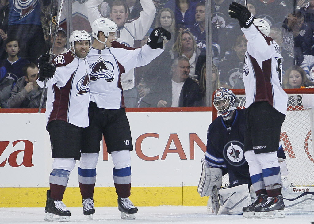 Colorado Avalanche's Maxime Talbot (25), Nick Holden (2) and Cody McLeod (55) celebrate Holden's goal against Winnipeg Jets' goaltender Al Montoya during the second period.