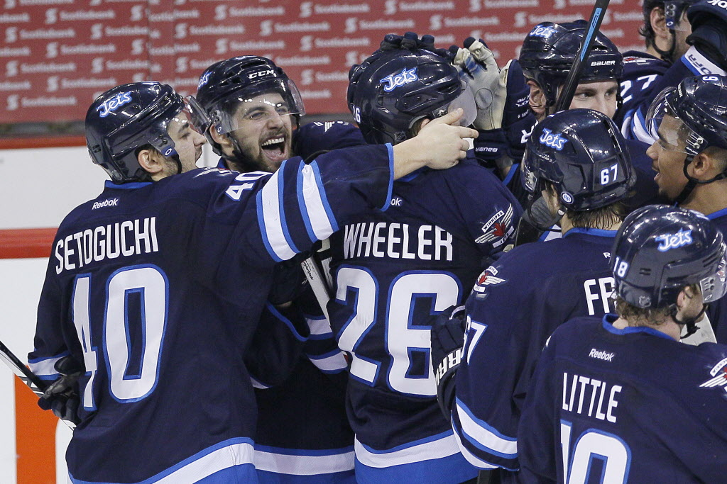 Winnipeg Jets' Devin Setoguchi  and Eric O'Dell celebrate Blake Wheeler's overtime goal against the Colorado Avalanche in NHL action in Winnipeg on Wednesday, March 19, 2014.