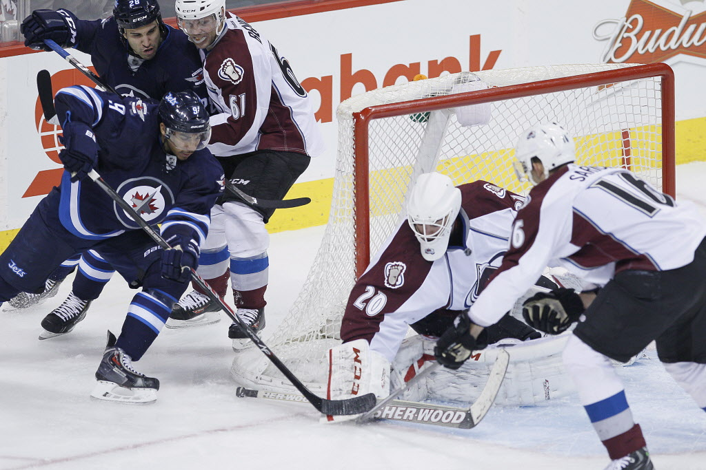Winnipeg Jets' Evander Kane gets shut down by Colorado Avalanche goaltender Reto Berra (20) and Cory Sarich (16) on the wraparound during the third period.
