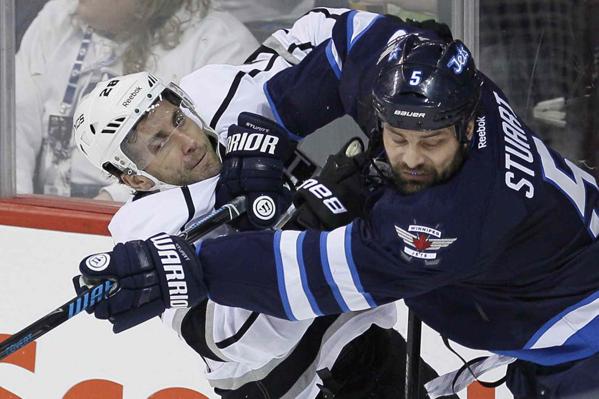 Winnipeg Jets' Mark Stuart (5) checks Los Angeles Kings' Jarret Stoll (28) during the first period in Winnipeg on Thursday.